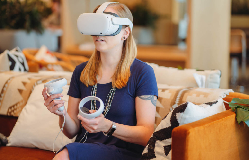 Woman with a VR headset and hand controllers